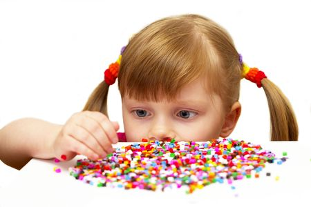 Little girl choosing colored details over white background Stock Photo