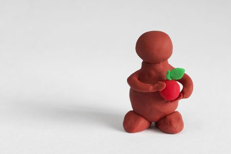 Plasticine man keeping a red apple over grey background photo