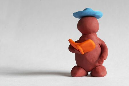 Plasticine man reading the book over grey background photo
