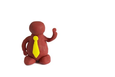 Plasticine man with a yellow tie keeping one hand up isolated over white background photo