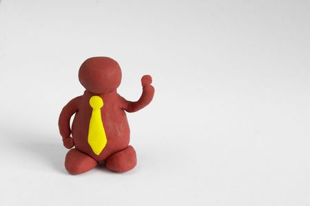 Plasticine man with a yellow tie keeping one hand up over grey background photo