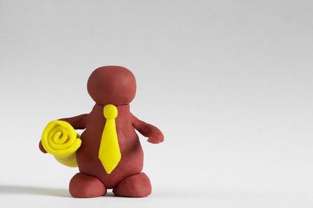 Plasticine man keeping a yellow roll over grey background photo