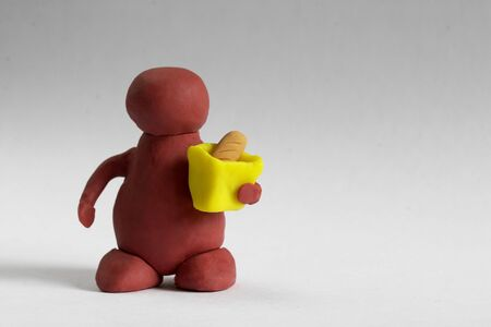 Plasticine customer keeping a bag with a bread over grey background photo