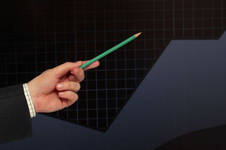 Pencil showing the growth of  profit over black graph photo