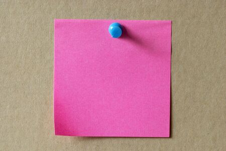 Pink sticker note with a blue push-pin over cardboard photo
