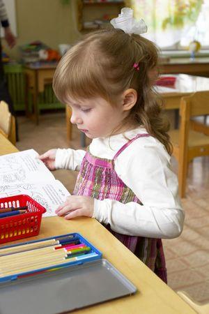 jardin de infantes: Ni�a leyendo un libro en la sala de jard�n kinder