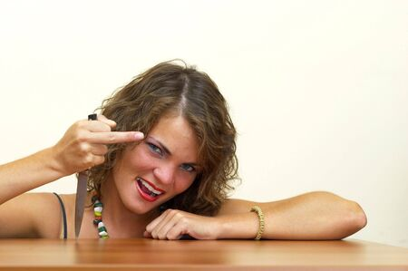 Young woman showing F. You! gesture with a knife in the hand photo