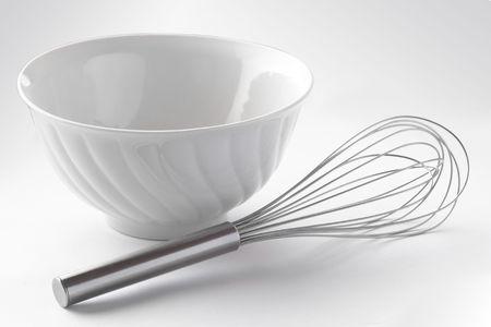 whisker: White porcelain bowl and metal whisker over white background Stock Photo