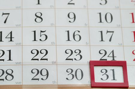 End of the month with red plastic mark frame on 31 digit calendar macro shoot photo