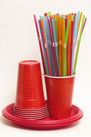 Wisp of colored plastic, stack of plastic cups and plates photo