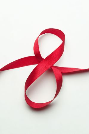 Red gift celebration ribbon in 8 digit shape over white background