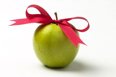 apple christmas: Green apple and red ribbon bow isolated over white background