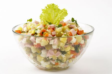 Russian salad (Olivie) isolated over glass bowl