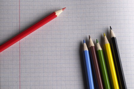 Colorful pencils set macro shot over checked paper background photo