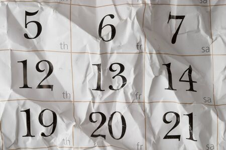 Friday the 13th crumpled calendar with scratches macro shot background photo