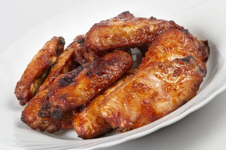 Chicken Buffalo Wings on the white plate over grey gradient background photo