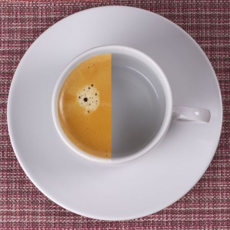 Little white espresso coffee cup on a white saucer over checked table-cloth background