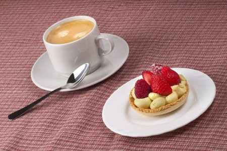 Little white espresso coffee cup and small berry tart over checked table-cloth background photo