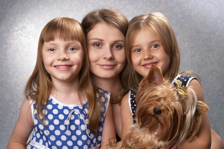 Young mother and two little sisters with Yorkshire terrier over light defocused background Stock Photo - 7416818