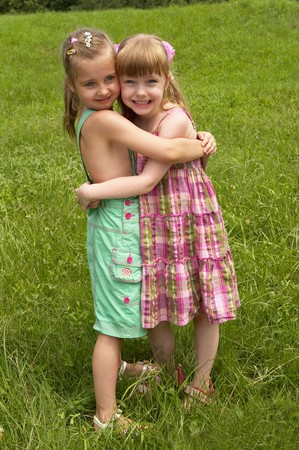Two little girls standing together in the park, one hugs another photo