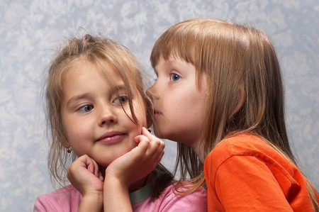 Two little girls one telling a secret to another over light defocused background photo