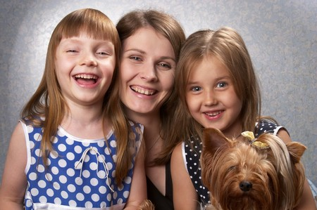 Young mother and two little sisters with Yorkshire terrier over light defocused background Stock Photo - 7533082