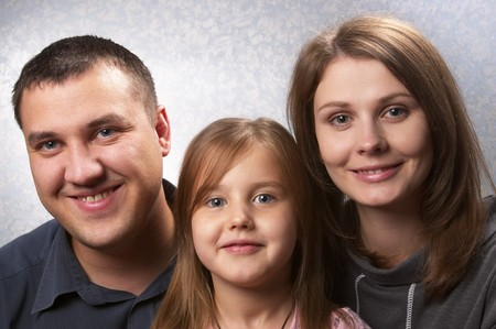 Young mother, father, and daughter over light defocused background Stock Photo - 7533075