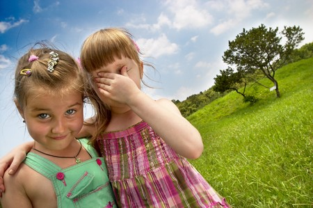 Two little girls in the summer park (one with closed eyes from bright light)