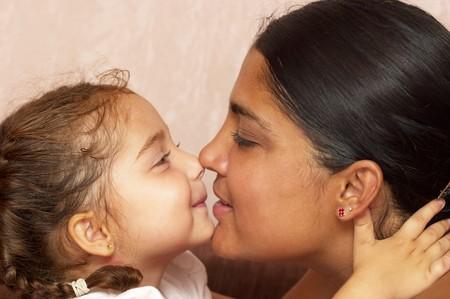 relaciones humanas: Joven madre y su peque�a hija sobre fondo de papel tapiz defocused  Foto de archivo