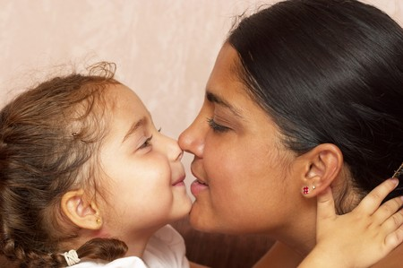 Young mother and her little daughter over defocused wallpaper background Stock Photo - 7533068