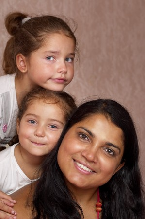 Young mother and two little sisters over defocused wallpaper background Stock Photo - 7533057