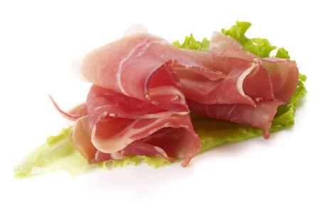 Jamon ham slices over leafs of lettuce macro shot