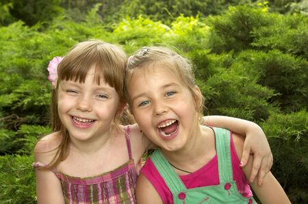 cute girlfriends: Two little girls standing together in the park, one hugs another Stock Photo