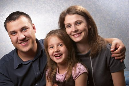 Young mother, father, and daughter over light defocused background Stock Photo - 7915755