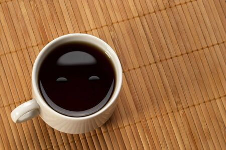 Little white espresso coffee cup on a bamboo mat (upprer view)