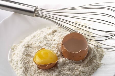 whisker: Flour pile, egg and metal whisker fragment over gray gradient background