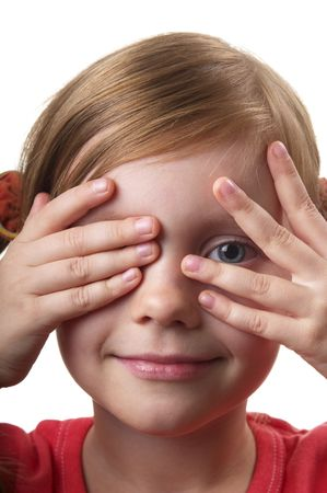 Little girl peep thru hand with one eye isolated over white background photo