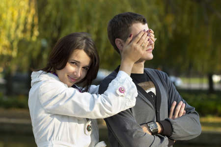 eyes closing: Young girl closing her boyfriend eyes with hands over defocused park background