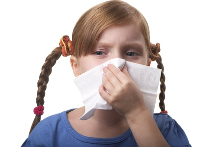 catarrh: Little girl blowing nose in tissue isolated over white background