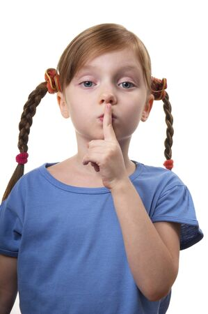 kidding: Little girl gesturing silence sign isolated over white background