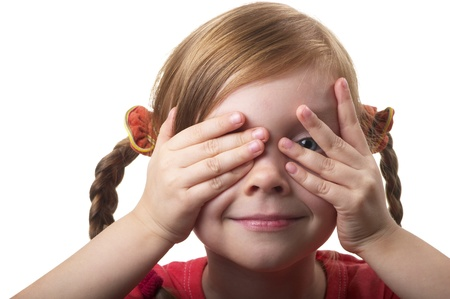 Little girl peeping through hand with one eye isolated over white background Stock Photo