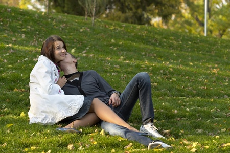 lying in leaves: Young couple sitting in the autumn city park (defocused background)