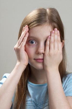 sneak: Schoolgirl peeping through hand with one eye over grey background