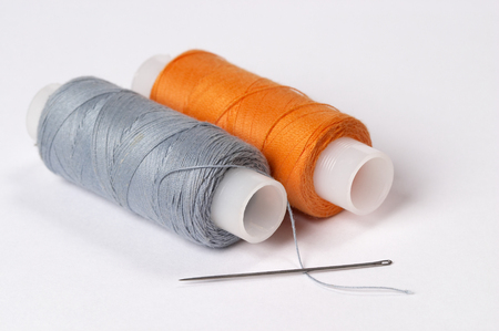 needle and thread: Two coils of thread grey and orange with needle over white background