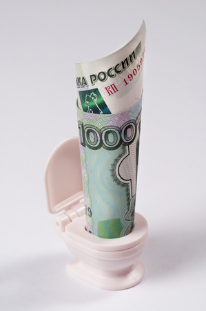 roubles: Russian one thousand roubles banknote rolled in smal toy toilet Stock Photo