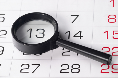 allocate: Black magnifying glass over slightly defocused calendar background