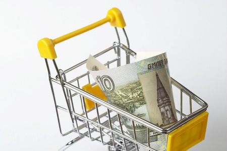 contain: Metallic shopping trolley fragment with ten rubles over white background