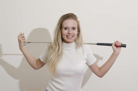 blonde girl holding golf club on her shoulders smiling photo