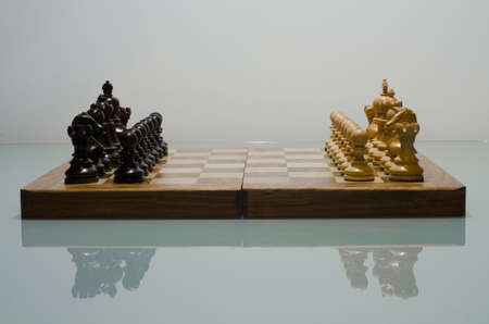 strategically: chessboard with pieces set up for play shoot on reflective surface in studio