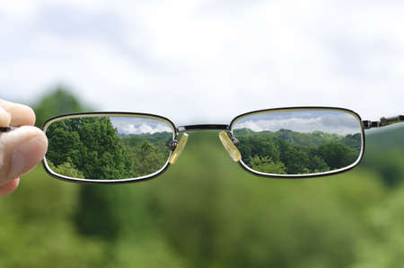astigmatism: out of focus nature with hand holding a glasses that correct the vision